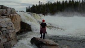 Situaci?n del hombre del viaje delante de la cascada en el bosque de Noruega en la madrugada Vestido en un sombrero rojo almacen de video