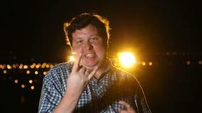 Situación del hombre y mostrar gesto de la roca en la noche al aire libre, retrato almacen de metraje de vídeo