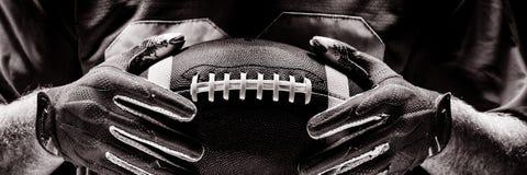 Situación del jugador de fútbol americano con el casco y la bola del rugbi fotos de archivo