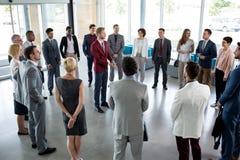 Situación del líder en círculo de su equipo acertado del negocio foto de archivo