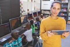 Situación del maestro con la tableta digital en sala de clase del ordenador fotos de archivo