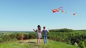 Situación del muchacho y de la muchacha encima de una colina con la cometa del vuelo metrajes