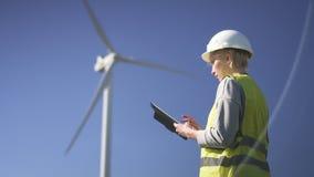 Situación del trabajador del cuello cerca del molino de viento y programa con sobre el dispositivo almacen de video