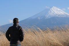 Situación del viajero del hombre y mirada del monte Fuji hermoso con el cielo capsulado y azul de la nieve el kawaguchiko del lag fotografía de archivo libre de regalías