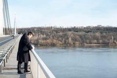 Situación deprimida y ansiosa sola del hombre en el puente con los pensamientos suicidas decepcionados en la gente que parece aba imagenes de archivo