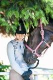 Situación ecuestre del adolescente joven cerca de su caballo marrón Imagen de archivo libre de regalías