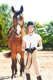Situación ecuestre del adolescente joven con su caballo marrón Fotografía de archivo