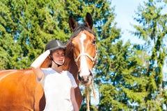 Situación ecuestre del adolescente joven con su caballo marrón Imagen de archivo