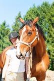 Situación ecuestre del adolescente joven con su caballo marrón Foto de archivo libre de regalías