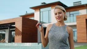 Situación emocionada de la mujer con llaves cerca del chalet Mujer hermosa que lleva a cabo llaves de la casa almacen de video