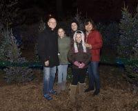 Situación exterior de los abuelos y de tres nietas delante de los árboles de navidad Fotografía de archivo libre de regalías