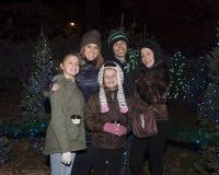 Situación exterior de los padres de mediana edad y de tres hijas delante de los árboles de navidad Foto de archivo libre de regalías