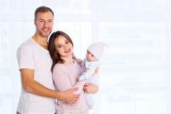 Situación feliz de la familia, de la madre y del padre con el hogar del bebé en el sitio blanco cerca de la ventana imagen de archivo libre de regalías