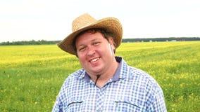 Situación feliz del granjero en el campo que guiña y que sonríe, sombrero de vaquero del desgaste en un día soleado almacen de metraje de vídeo