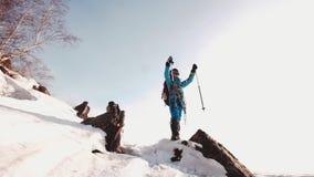 Situación feliz del montañés en el top de montañas cubiertas con nieve, en las manos de los polos de esquí en la cabeza las gafas almacen de video