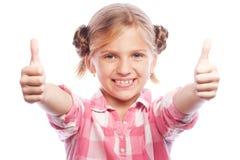 Situación feliz del niño de la niña aislada sobre el fondo blanco Mirando la cámara que muestra los pulgares para arriba Foto de archivo