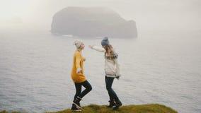 Situación feliz loca de la mujer dos en la orilla de un mar y de un baile junto Turistas que se divierten en Islandia almacen de metraje de vídeo
