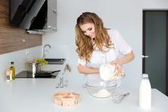 Situación feliz y el cocinar de la mujer bastante joven Imágenes de archivo libres de regalías