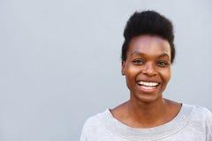 Situación femenina africana alegre contra fondo gris Fotos de archivo libres de regalías