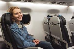 Situación femenina alegre en silla en el avión Foto de archivo libre de regalías