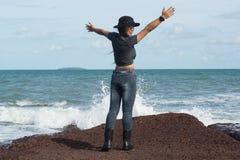Situación femenina bonita asiática en rocas con las ondas fuertes imágenes de archivo libres de regalías