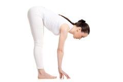 Situación femenina de la yogui en la actitud de Uttanasana Foto de archivo