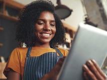 Situación femenina del barista en cafetería usando la tableta digital imagen de archivo libre de regalías