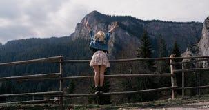 Situación femenina joven al borde del acantilado y aumento de sus manos para arriba contra las altas montañas rocosas Muchacha fe almacen de video