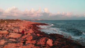Situación femenina joven del fotógrafo en las fotos rocosas de la costa y el tomar de olas oceánicas hermosas en la puesta del so almacen de video