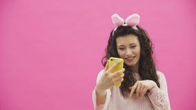 Situación hermosa de la chica joven en un fondo rosado Durante esto, hay oídos de conejos en la cabeza almacen de metraje de vídeo