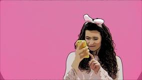 Situación hermosa de la chica joven en un fondo rosado Durante esto, hay oídos de conejos en la cabeza Hace una foto de