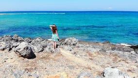 Situación hermosa de la mujer en la orilla de mar y la mirada en las ondas de agua azul, Creta metrajes