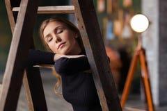 Situación hermosa de la mujer joven, inclinándose en la escalera indoor d imagen de archivo