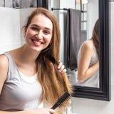 Situación hermosa feliz de la mujer joven, cepillando su cabello seco largo Imagen de archivo