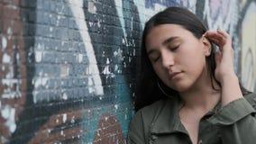 Situación hermosa joven de la muchacha cerca de la pared con la pintada y presentación mirando la cámara con una mano a través de almacen de metraje de vídeo