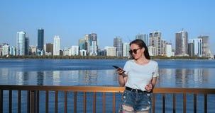 Situación hermosa joven de la muchacha en la costa en el fondo de la ciudad que sostiene un smartphone metrajes