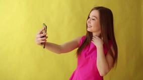 Situación hermosa joven de la señora aislada sobre fondo amarillo mientras que haga el selfie por el teléfono almacen de video