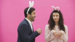 Situación hermosa joven de los pares en un fondo rosado Durante esto hacen los movimientos de conejos La mujer la puso almacen de metraje de vídeo