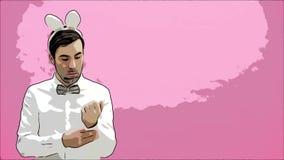 Situación hermosa joven del hombre en un fondo rosado Vestido en una camisa blanca con los oídos de conejo en su cabeza Poner una