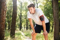 Situación joven cansada del deportista y relajación después de correr en bosque Imágenes de archivo libres de regalías