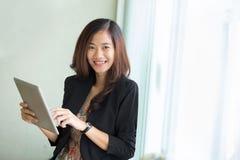 Situación joven de la empresaria mientras que mirada en una PC de la tableta Fotografía de archivo
