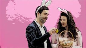 Situación joven de los pares derecha en fondo rosado Con los oídos de un conejito en la cabeza Durante este hombre da a su esposa almacen de video