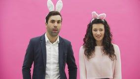 Situación joven de los pares derecha en fondo rosado Durante este tiempo, se visten en oídos de la barra de pudelar Mirada de cad almacen de video