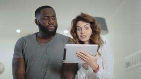 Situación joven de los pares en la sala de estar con la tableta junto almacen de video