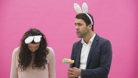 Situación joven de los pares en un fondo rosado Durante este hombre sostiene los huevos de Pascua en sus manos, su esposa bajó su