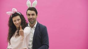 Situación joven de los pares en un fondo rosado Durante esto, miran la cámara y muestran un gesto de la llamada Feliz