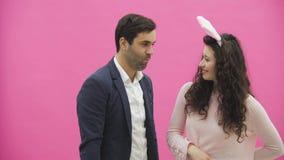 Situación joven de los pares en un fondo rosado La esposa de un conejo rosado en su cabeza, sosteniéndose en sus oídos de conejo