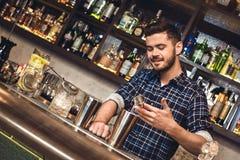 Situación joven del camarero en el alcohol de colada del contador de la barra en la coctelera alegre foto de archivo