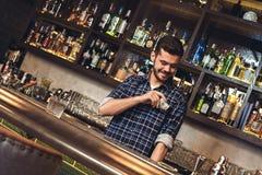Situación joven del camarero en el contador de la barra que pone billetes de banco en el bolsillo satisfecho imagenes de archivo