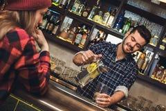 Situación joven del camarero en la sonrisa de colada de servicio del vaso de agua del cliente del contador de la barra fotografía de archivo